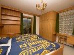 Slaapkamer met 2-persoonsbed en wastafel. Slaapkamer heeft toegang tot het balkon.