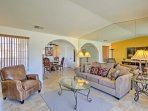 A comfortable sofa and leather armchair offer ample seating around the large flat-screen TV.