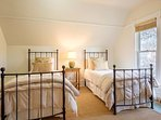 This bedroom has twin beds and can be accessed from the master's French doors or the hallway.