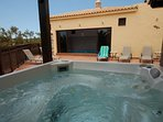Hot tub - looing at the pool room.  The pool room doors slide open. Full sunshine or shade!