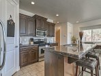 The kitchen features dark wooden cabinetry, granite countertops and stainless steel appliances.