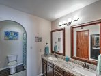 This full bathroom features a double vanity and granite countertops.