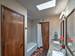 This full bathroom features granite countertops and a shower/tub combo.