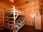 Downstairs bedroom features full size bunk beds with access to bathroom with walk-in shower