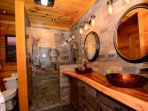 Main level bathroom accessed from bedroom or hallway for guests features double vanity and large walk-in shower.