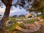 Garden and sea view in the sunset. Stone built bench - Villa Russelia in Rhodes