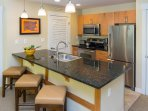 with stainless steel appliances and breakfast bar with seating for three