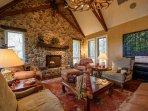 Soaring ceiings & warm river rock & rich wood floors