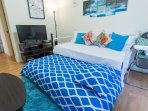The bedroom is furnished with a full bed, complete with plenty of pillows and fresh linen & sheets