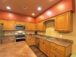 The fully equipped kitchen features new stainless steel appliances and a center-island chopping counter.