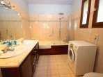 On-suite bathroom with shower over bath and washing machine.