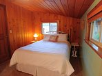 Guest bedroom with wood clad walls and ceiling. Queen bed with hotel comforter and duvet