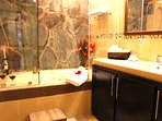 Luxurious bathroom with relaxing tub, large counter and glass shower.