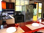 Fully equipped kitchen with stove, oven, fridge, small appliances and place settings.