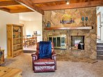 Beamed ceilings and a large stone wood-burning fireplace create a cozy cabin feel.