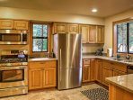 The fully equipped kitchen features stainless steel appliances and plenty of counterspace for preparing meals.