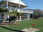 Beautiful manicured yard with horseshoe pit, four swings, grass and steps away from the beach!