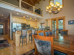 From the kitchen island and breakfast bar, visit with those in the loft above, the dining room, or the open living...