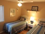 Comfortable twin beds in sunny guest room.