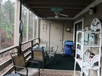 Large screened porch has dining area and cart with beach chairs & umbrella.