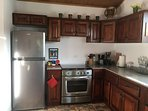 Large refrigerator, 6 burner gas stove, microwave, toaster oven, knife block, cookware & storage.