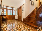 Hallway with original pitched pine stair case and geometric tiles.