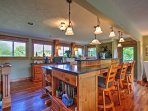 The kitchen features updated appliances and countertops, along with a spacious center island that doubles as an eating...