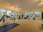Enjoy a daily workout in the fitness room over looking lush landscaping, resort pool, and Estero Bay.