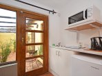 Kitchenette with fridge, microwave, wash up area and door to courtyard.