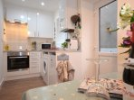 Fully fitted white kitchen/diner with wash machine, pod coffee maker, microwave etc.