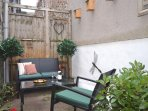 Private, enclosed courtyard with seating, BBQ, pretty plants, accessed from kitchen.