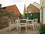 Private patio with St Thomas Church spire in background. Gate to parking area. All weather furniture