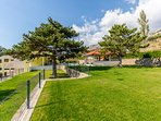 Spacious grass plot as playground next to summer kitchen