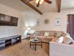 Relax in the spacious living area featuring a brick fireplace and exposed beams.