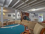 The area features an air hockey table, ping pong table, pool table, foosball table, and a poker table.