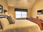 This master suite features a queen-sized bed and flat-screen cable TV.