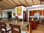 Modern gourmet kitchen with top-tier appliances, granite counter tops, and wraparound bar seating.