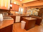 Kitchen: granite countertops, propane stove, island.  Breakfast bar to right.