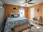The second bedroom features a bright pop of color and a comfortable queen-sized bed.