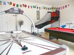 Games room with air hockey, pool table with table tennis top and basketball game