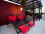 Shaded poolside pergola with  seated and sunbathing area.