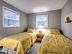 This bedroom provides 2 twin beds with light and bright comforters.