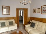 Comfortable living room with traditional fireplace & TV with doors opening onto front balcony