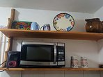 Microwave, toaster, kettle, cooktop and refrigerator with freezer provided in the kitchen.
