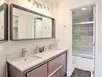 The bathroom has a dual sink vanity and separate shower/tub combo with toilet.