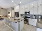 A Chef's kitchen featuring glass cooktop stove, oven, refrigerator with water & ice dispenser, dishwasher and plenty of...