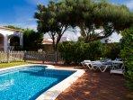 Gran piscina privada con mobiliario de exterior, hamacas, sombrilla