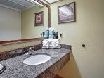 The single vanity features granite counters and a large mirror to utilize.
