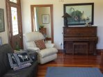 Lounge with lazy boy and leather couch. Piano and