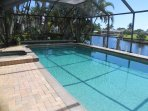 Large solar-heated pool and spa with screened lanai and view of intersecting canals